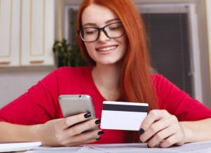 woman smiling with phone and card