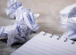 scrunched up paper and notepad