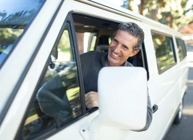 man smiling in car