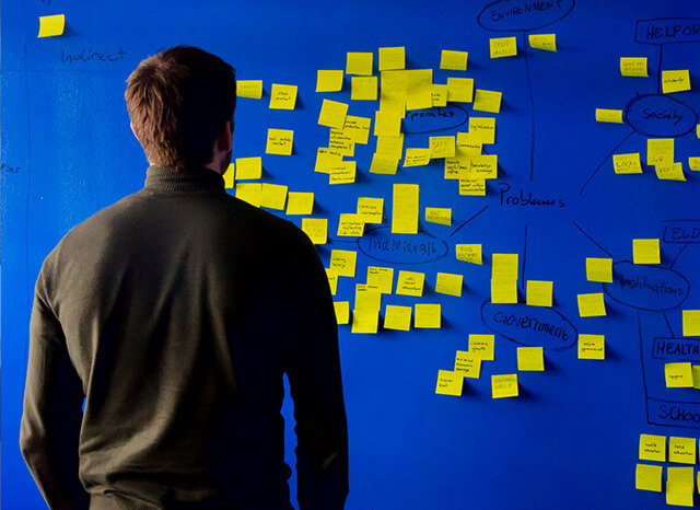 man looking at postit notes
