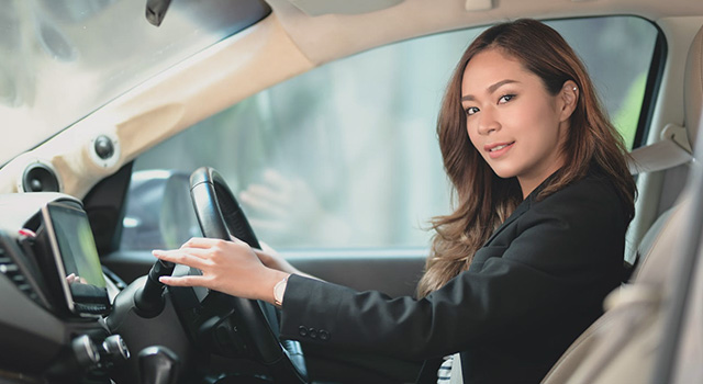 woman driving and smiling